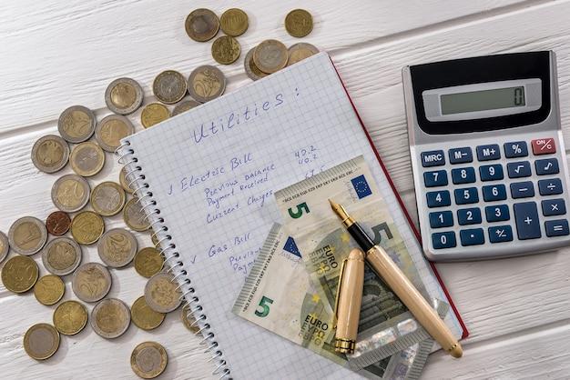 Notas e moedas de euro com bloco de notas e calculadora
