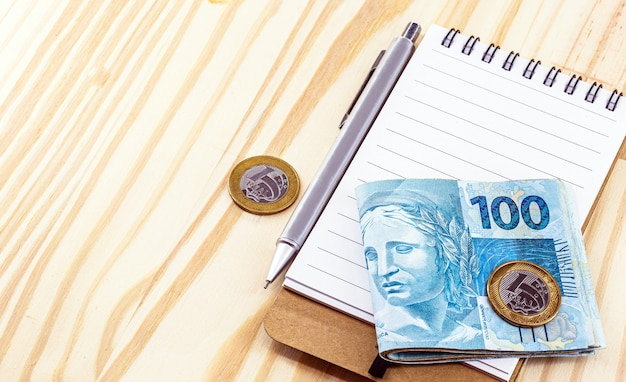 Notas e moedas do dinheiro do brasil, na mesa com bloco de notas e caneta