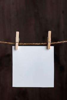 Notas em branco brancas com prendedores de roupa na corda em fundo de madeira. copie o espaço. espaço para seu texto. quadro vertical.