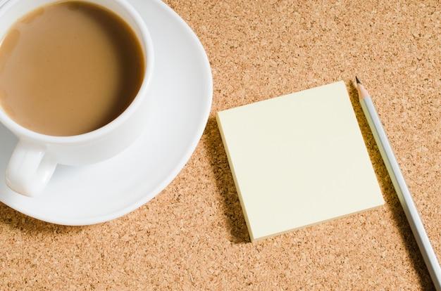 Notas em branco e café na placa de cortiça