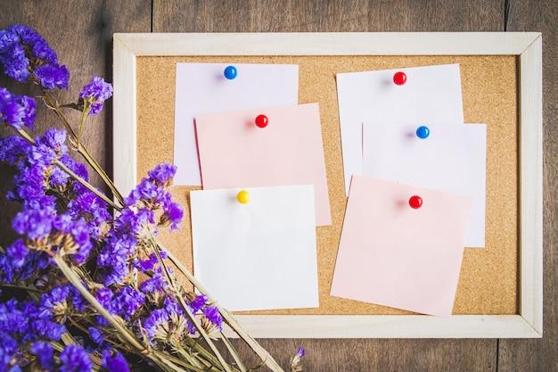 Notas em branco na placa de cortiça com buquê de flores secas