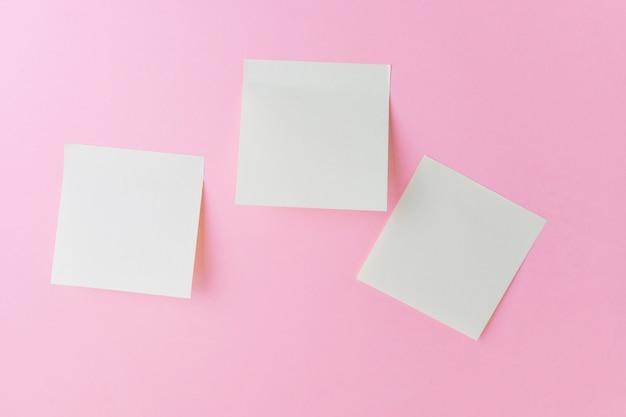 Notas em branco sobre um rosa pastel.