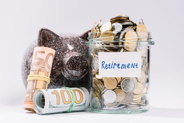 Notas enroladas; piggybank e aposentadoria recipiente cheio de moedas no pano de fundo branco