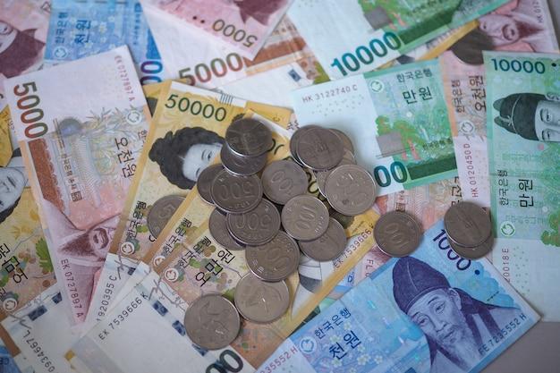 Notas ganhadas coreanas e moedas ganhadas coreanas por fundo do conceito de dinheiro