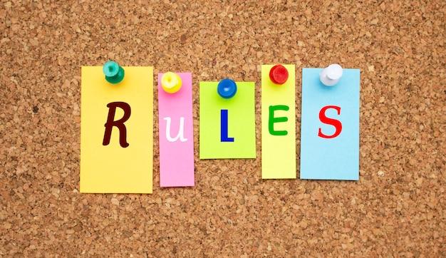 Notas multicoloridas com letras fixadas em um quadro de avisos de cortiça.