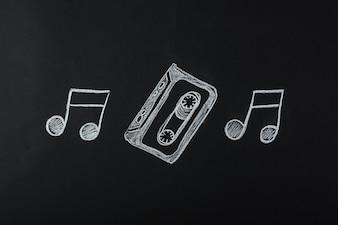 Notas musicais desenhadas com fita cassete no quadro-negro