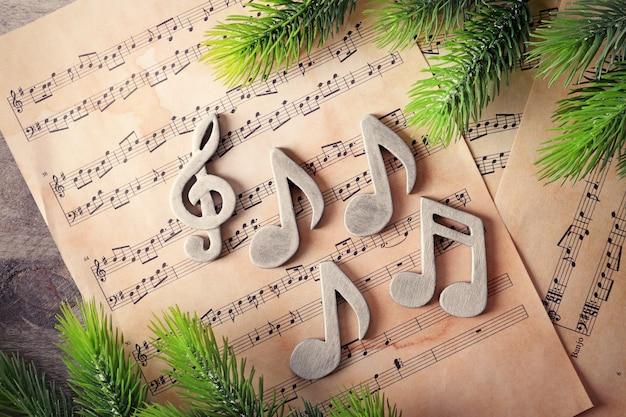 Notas musicais e árvore de natal em fundo de madeira