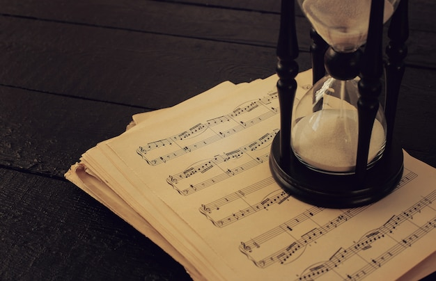 Notas musicais em papéis e ampulheta