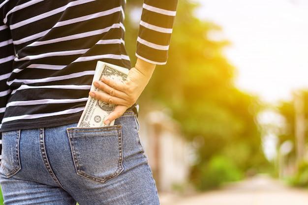 Notas no bolso da calça jeans de uma mulher. - compre e economize para o futuro conceito.