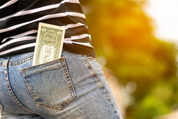 Notas no bolso da calça jeans de uma mulher.
