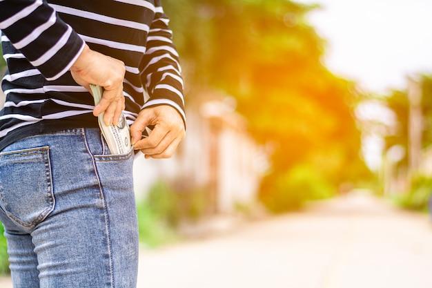 Notas no bolso jeans de uma mulher