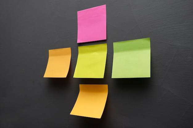 Notas pegajosas coloridas em branco na parede do escritório
