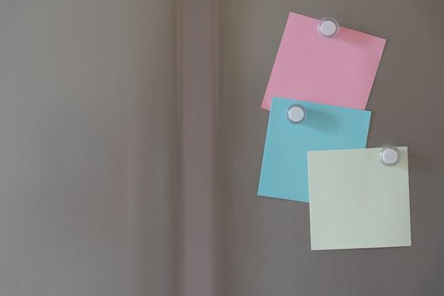 Notas pegajosas ímã colorido no fundo da porta da geladeira