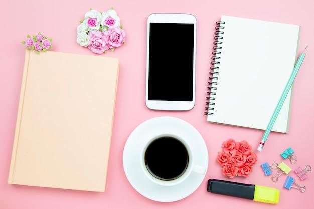 Notebook celular e café preto copo branco rosa fundo