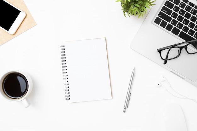 Notebook com a página em branco é no meio da mesa de mesa de escritório branco com suprimentos.