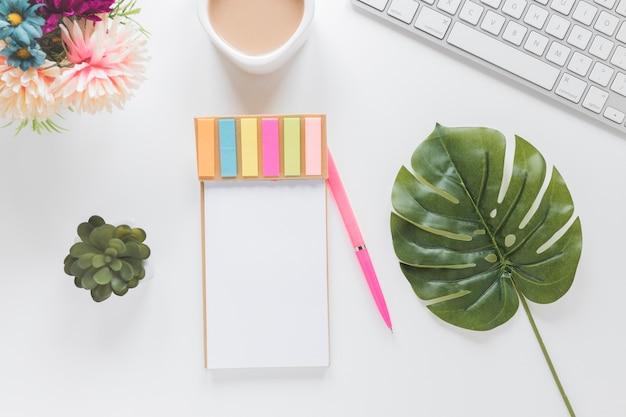 Notebook com adesivos perto de xícara de café, teclado e plantas