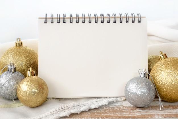 Notebook com bola de natal de ouro e prata na mesa de madeira