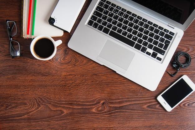 Notebook com café quente na mesa de madeira
