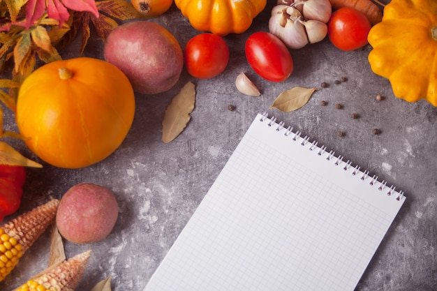 Notebook com folhas de outono e legumes no fundo de concreto