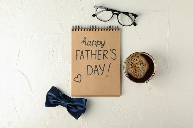 Notebook com inscrição feliz dia dos pais, gravata borboleta azul, xícara de café e copos no fundo branco