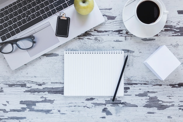 Notebook com lápis perto de xícara de café e laptop