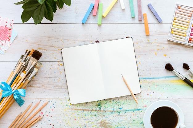 Notebook com materiais de arte na mesa de madeira branca