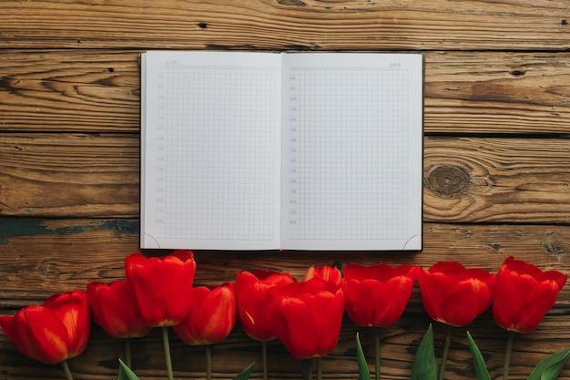 Notebook com páginas brancas e linha vermelha de tulipas no fundo de madeira