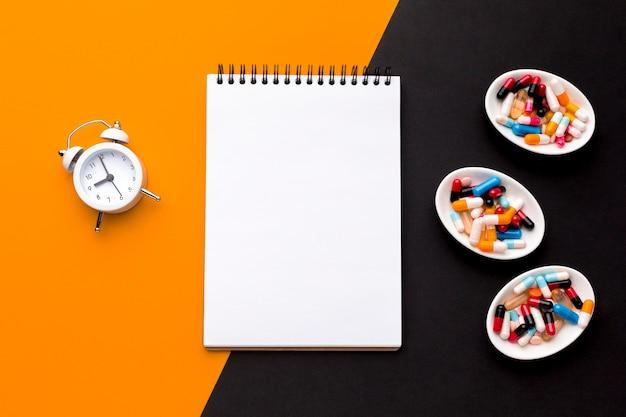 Notebook com pílulas e relógio