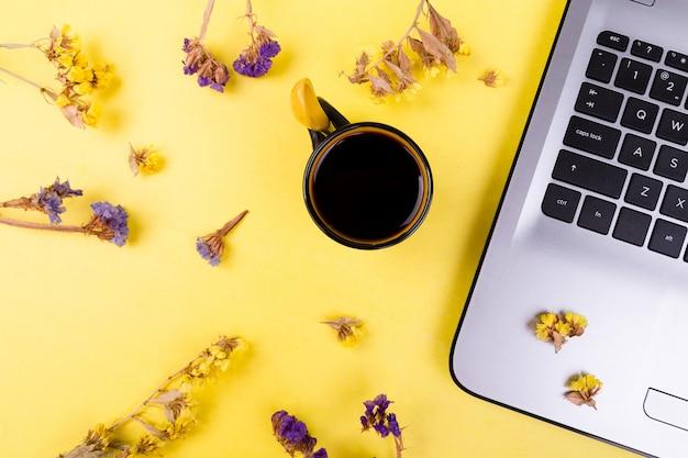 Notebook com xícara de café e flores em um local de trabalho em fundo amarelo