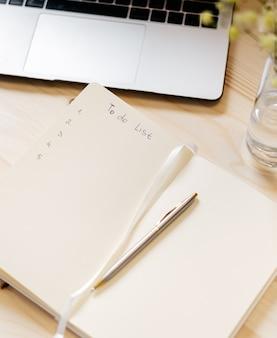 Notebook de papel em branco de vista superior com lista de tarefas, flores, teclado de laptop, xícara de café e caneta.