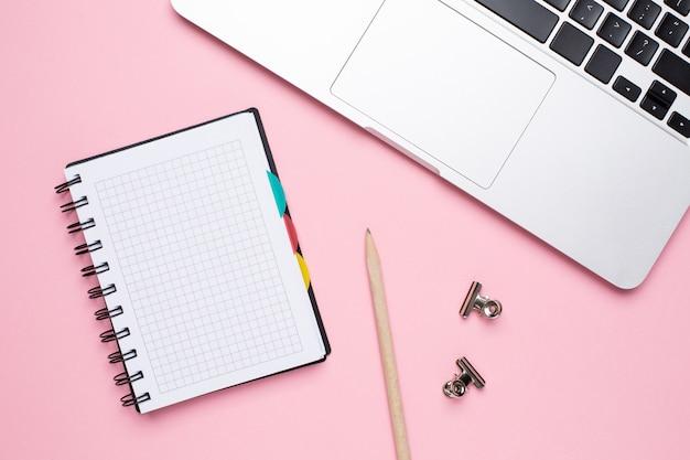 Notebook e laptop em um fundo rosa
