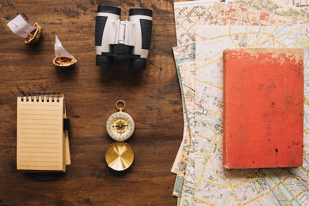 Notebook e material turístico perto de livro e mapas
