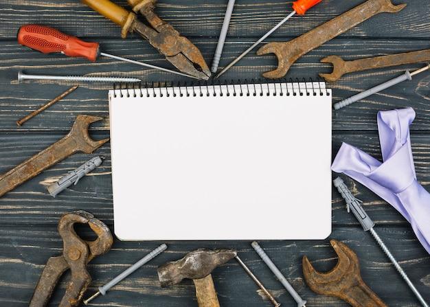 Notebook entre conjunto de equipamentos de reparação e gravata