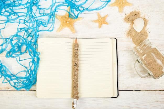 Notebook, estrelas do mar e conchas, vidro com areia