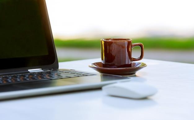 Notebook laptop com café quente na mesa de madeira.