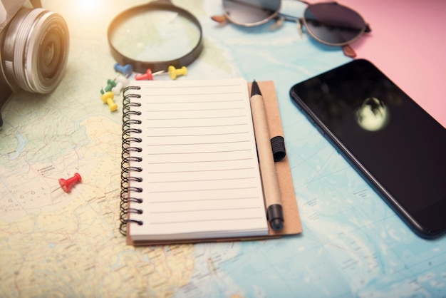 Notebook mockup planejamento turístico férias com outros acessórios de viagem ao redor.