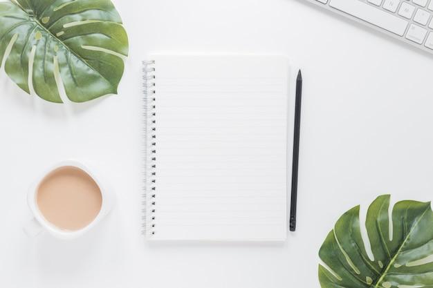 Notebook perto da xícara de café e teclado na mesa com folhas verdes