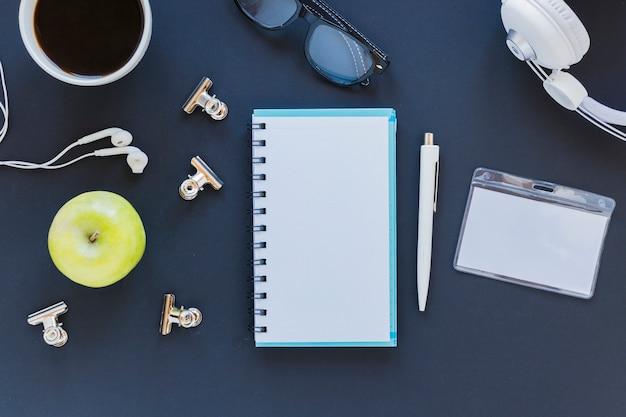 Notebook perto de artigos de papelaria e dispositivos eletrônicos
