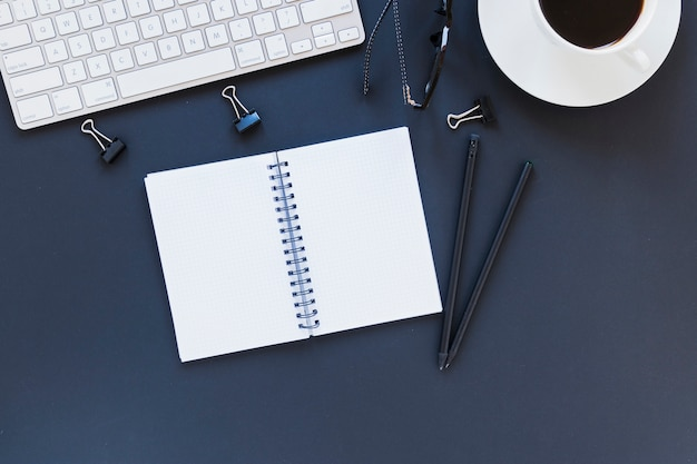 Notebook perto de artigos de papelaria, teclado e conjunto de chá