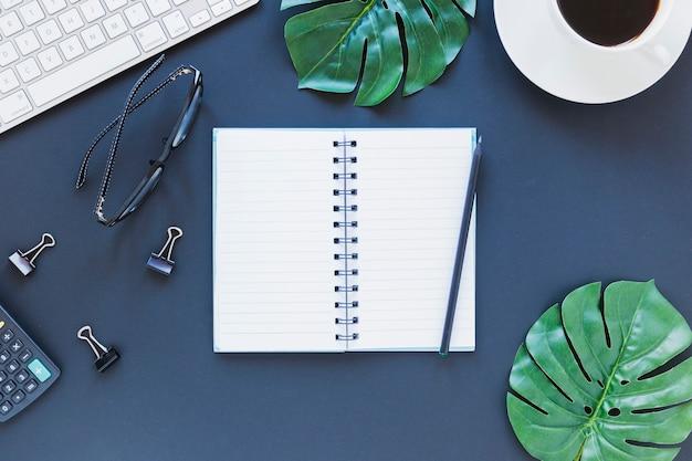 Notebook perto de artigos de papelaria, teclado e óculos na mesa azul escura com clipes de calculadora e fichário