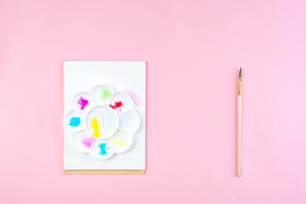 Notebook simulado para obras de arte com tintas aquarela, paleta e um pincéis.
