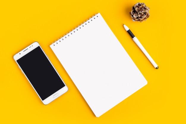 Notebook, telefone, celular, chá, caneta, óculos em um fundo amarelo