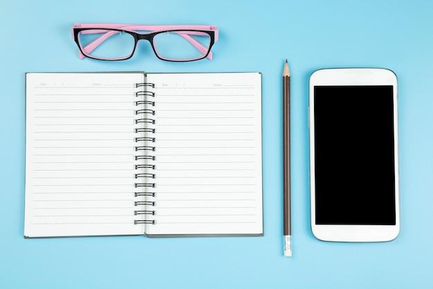 Notebook telefone celular no estilo pastel de fundo de óculos rosa blye