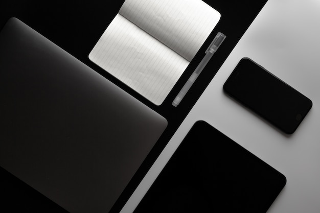 Notebook, telefone e tablet na mesa de escritório em preto e branco