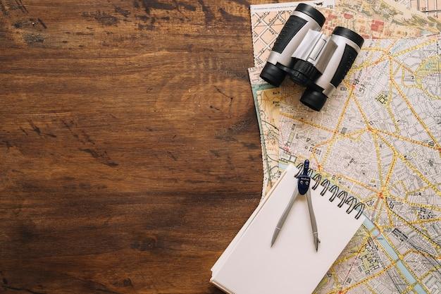 Notebook uma bússola perto de binóculos e mapas