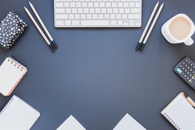 Notebooks perto de calculadora e teclado na mesa com uma xícara de café