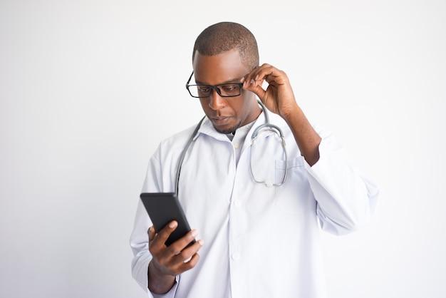Notícia masculina preta séria da leitura do doutor no smartphone. Foto gratuita