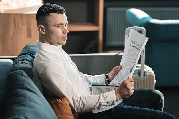 Notícias da manhã. homem de negócios bonito de calça quadrada lendo o noticiário da manhã em seu escritório