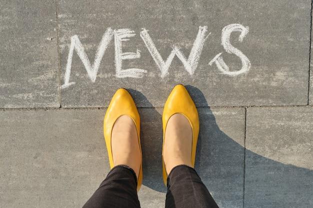 Notícias da palavra na calçada cinza com pernas de mulheres, vista superior