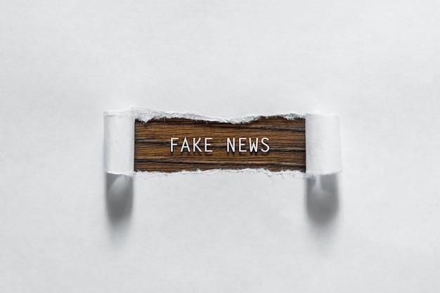 Notícias falsas - uma inscrição em um papel branco rasgado